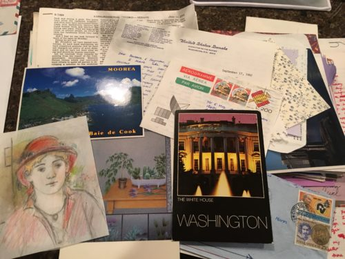 Pile of postcards and letters written by Margo and saved by Barbara. There's a postcard from Washington D.C. on the right; a postcard from Tahiti in the middle on the left; and a colored pencil drawing of Margo on the lower left. At the top is the upper half of a printout from the Congressional Record and a typed letter written on U.S. Senate Budget Committee stationary.