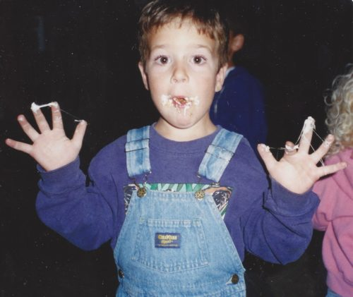 Jimmy in light blue overalls wearing a long sleeve purple shirt. He has a s'more in his mouth with marshmallow on his face and the fingers of both hands which he's holding up on either side of his face.