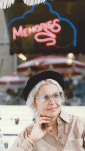 """Barbara wearing a navy blue hat and glasses with her right hand resting under her chin. She's a wearing a long sleeve tan blouse and is sitting under a neon pink sign that says """"Memories"""""""
