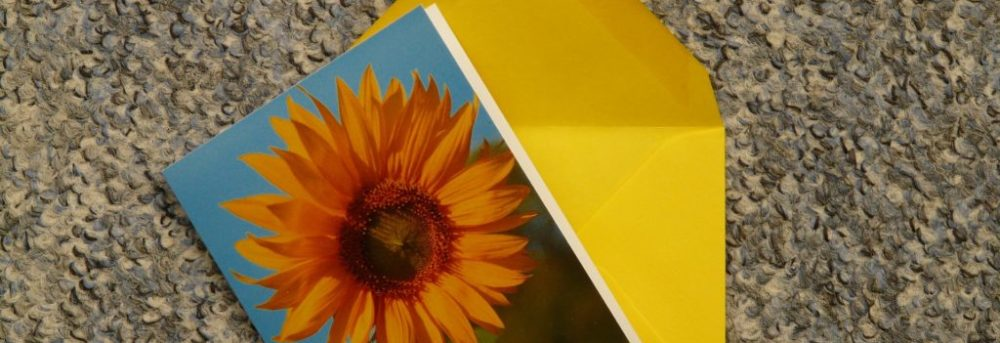 Card with sunflower on it with blue sky in the background sitting on yellow envelope with the flap open