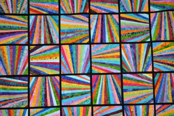 photo of the squares of a quilt. Each square has a dozen stripes of color widening out from the same area of the square.