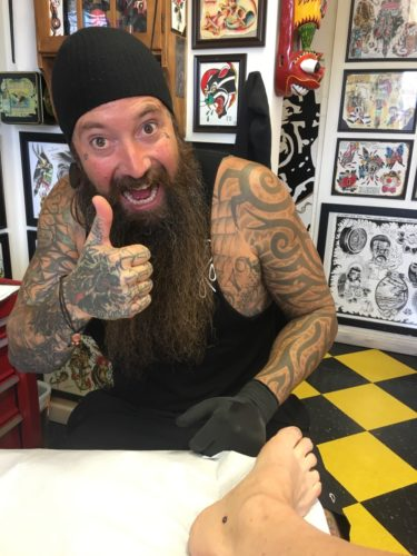 Tattoo artist covered with tattoos with a mustache and long beard and a blank tank top. He's sitting in front of a table with a bare foot on it. There's a black circle just below the ankle bone.
