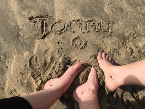 """Tommy"" and a circle below it written in the sand with three bare feet below the writing, all with black circles on below the ankle bone."