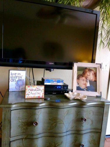 Jack's dresser with a big screen TV over it. The DVR with three videos is sitting under the TV. There's a photo of Ann & Jack on the right. On the left are two motivation sayings