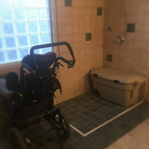 Jack's wheelchair parked in front of a window in the shower. To the right is the tub of Jack's belongings that came home with Ann after Jack died and the shower itself