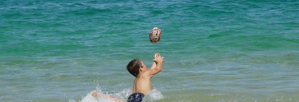 Jimmy is in the ocean wearing swim trunks. His arms are outstretched, reaching to catch a football.