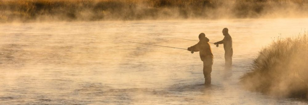 Two fly fishermen standing to the right of the photo with their lines int the water. There's steam rising from the water and brown grass on the bank behind the water.