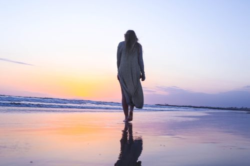 Woman walking on the beach at sunset. She's wearing a long sweater and is barefoot. The sky is pale orange and light purple and is reflected in the wet sand.