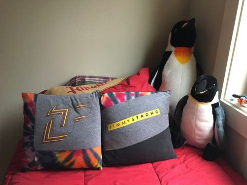 JF logo and JimmySTRONG on two throw pillow on Jimmy's bed which is covered with a red comforter. To the right of the pillows are two penguins, one taller than the other