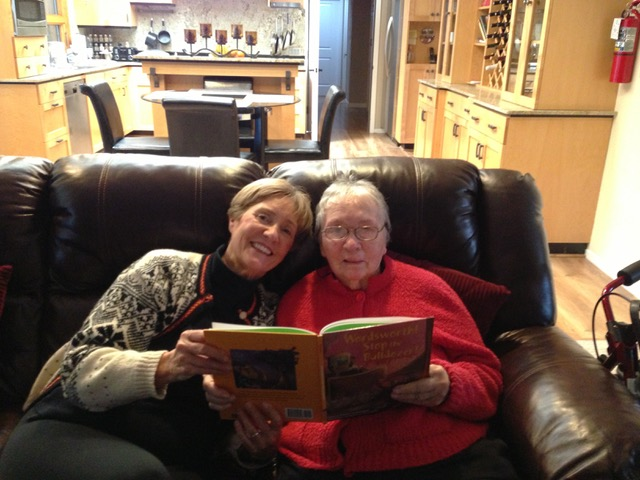 Diane and her mom are sitting on a brown leather couch in the living room, each holding the side of an open book. Diane is on the left wearing a black and white Christmas sweater. Diane's mom is on the right wearing a red sweatshirt.