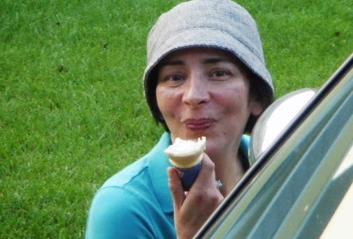 Donna wearing a turquoise colored shirt and a gray bucket hat eating vanilla ice cream cone in a game