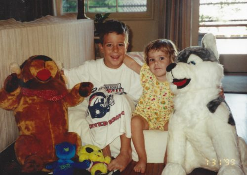 Jimmy and Molly sitting on a mattress with two large stuffed animals, a bull and a white dog on either side of them. Jimmy is wearing a long white tshirt with the Denver Broncos on it and Molly is wearing a yellow onsie
