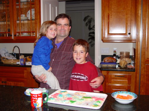 Dan holding Molly with his left arm around Jimmy. They're standing in front of a tray of homemade decorated Christmas cookies, a mug that says Milk for Santa and a bowl of carrots. Molly is wearing a long-sleeve blue shirt and khaki pants, Dan is wearing a brown checked shirt; Jimmy is wearing a long sleeve red t-shirt with Stanford on the front.