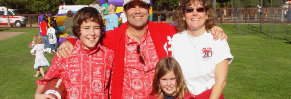 Jimmy, Dan, Molly & Margo at Big Game. Jimmy and Dan are wearing Stanford Hawaiian shirts. Jimmy is wearing black shorts; Dan is wearing white khakis and a Stanford hat. Molly is wearing a Stanford football jersey with the number 5 on it and black shorts. Margo is wearing a white short-sleeved t-shirt, white shorts and sunglasses and she has a red jacket tied around her waist.