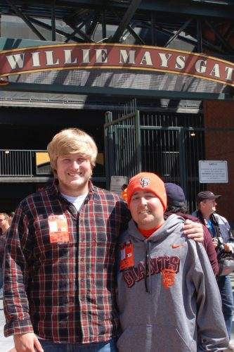 Jimmy and Griffin at the AT&T Park. They're standing under the Willie Mays Gate sign. Griffin is on the left. He has blond hair and is wearing a checked, long sleeve button shirt with a white t-shirt showing at the top. He has his left arm around Jimmy. Jimmy is wearing an orange SF Giants skull cap and a gray hoodie with an orange SF Giants across it