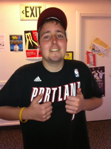 "Jimmy in his dorm. He's wearing a black t-shirt that says PORTLAND across the chest. He's wearing a baseball cap, LIVESTRONG band and is doing ""thumbs up"" with both hands"
