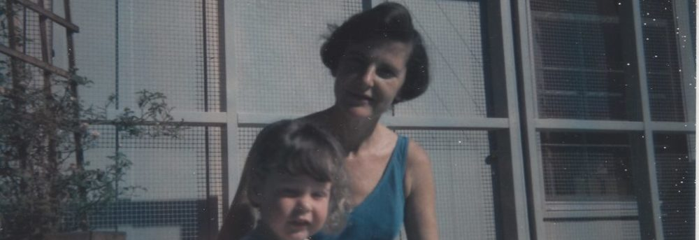 Mom wearing a teal one piece bathing suit, sitting at the edge of our pool with her right arm around me. I was about 2 and am wearing a light blue one piece bathing suit. There's a wire and wood fence behind us