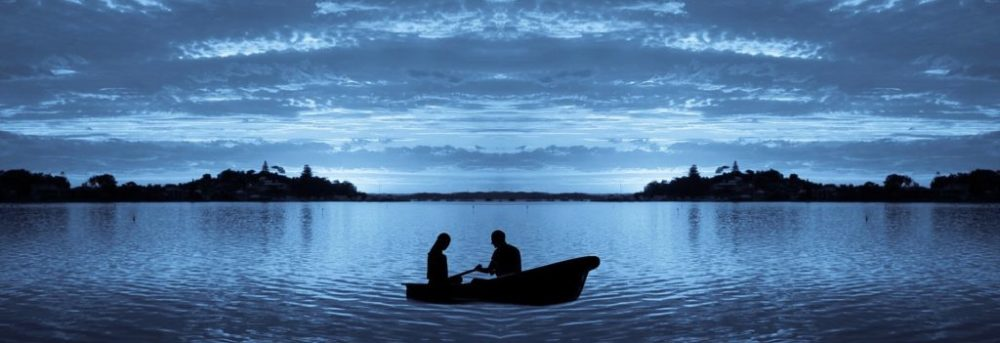 The silhouette of two people in a rowboat. The one on the left appears to be a woman; the one on the right who is rowing appears to be a man. The sun has set and the water and the cloudy sky are a deep blue gray.