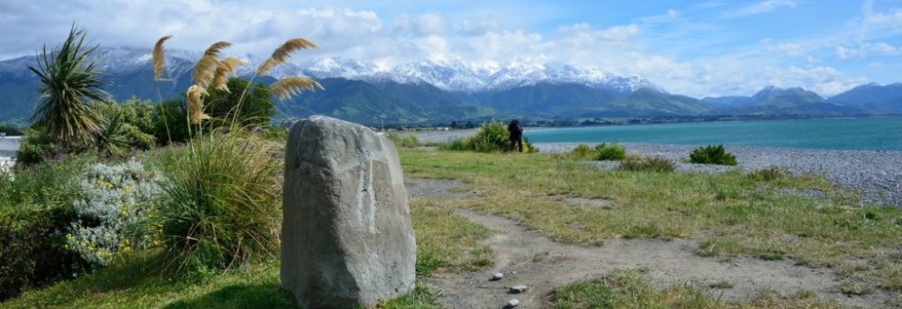Vertical piece of stone sitting next to a dirt path in a grassy area. In the distance, you can see a turquoise body of water, a line of mountains and cloudy skies above.