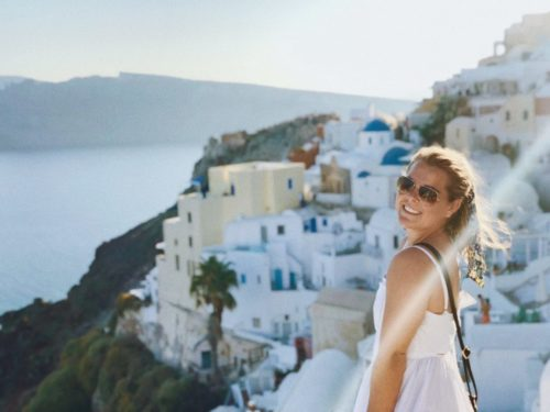 Molly on Santorinini. She is standing in front of the town looking back over her left shoulder toward the camera. She's wearing a white dress with spaghetti straps and sunglasses with her purse over her left shoulder and across her body. The town is in front of her to the left in the photo and the ocean and distant island are visible in the top left of the photo.