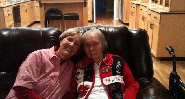 Diane sitting on a black leather couch with her mother. Her mother's kitchen with light wood cabinets can be seen in the background. Diane is on the left wearing a light red collared blouse over a long sleeve red t-shirt. Dian's mom is wearing dark pants, a white shirt and a red and black Christmas sweater.
