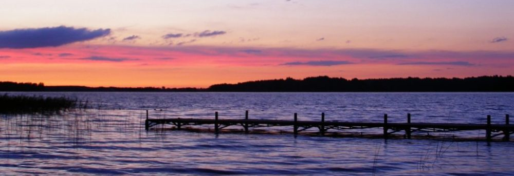 Lake in Masuria, Poland at sunrise. The sky and water are light and darker purple respectively. The clouds in the horizon are red and orange. There's a wooden dock stretching from the lower 1/3 of the photo on the right 3/4 away across the photo toward the left side