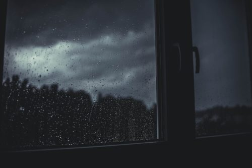 Rain and dark cloudy skies at night outside a window. the handles to open the window are visible on the right side of the photo