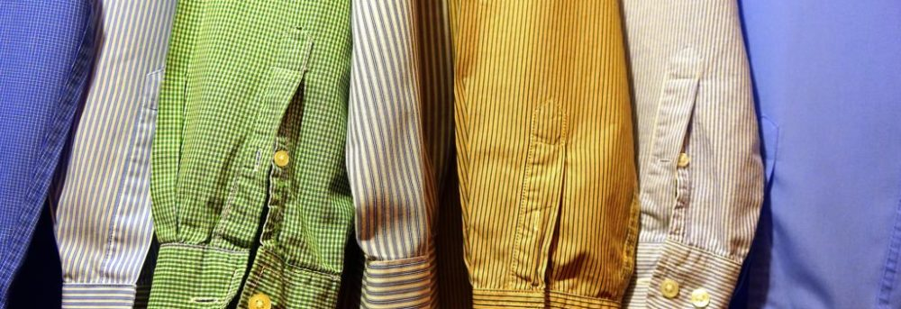 A row of men's button shirts hanging in the closet. Only the sleeves are visible in the following colors -- blue, white, light green, tan, goldenrod, tan, blue