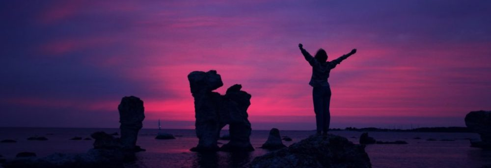 Silhouette of a female standing on a rock with other tall rock towers to her left. She has her arms outstretched in the shape of a Y. The sun is setting and the sky is red and blue and purple