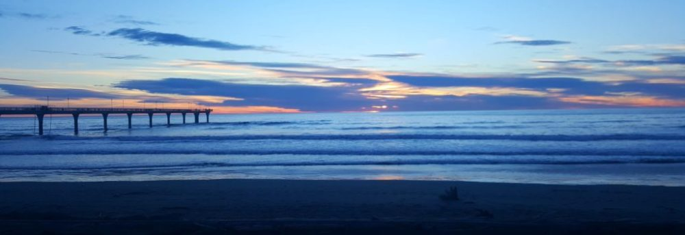Beach in New Zealand at sunset. The beach is dark blue, the ocean is blue with waves of dark blue. There's a dock on the left side. The clouds are dark blue with patches of orange and some blue sky above them