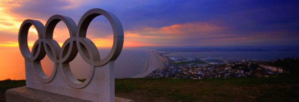 A sculpture of the olympic rings sitting on a hill above the ocean at sunset