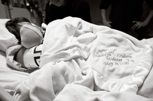 Crystal laying on a hospital bed with a blanket over her. She is holding Madelyn, who is wearing a knit cap, in her right arm.