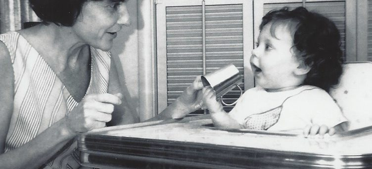 Margo age 1 sitting in her high chair putting a toy close to her mouth. Her hair is dark and she's wearing a white shirt. Her mom is kneeling down next to the highchair wearing a no sleeve summer dress. She has dark hair. There are shutters behind them hiding the washing machine. The photo is black and white.