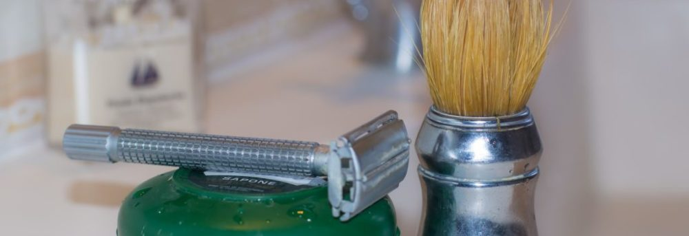 Man's silver razor lying on top of a small green circular container. Sitting next to it is a shaving cream brush with a silver handle