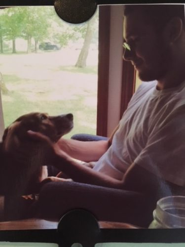 Jordan sitting in a chair in front of a window wearing white tshirt. His hands on either side of his dog's face and the dog is looking up at him.