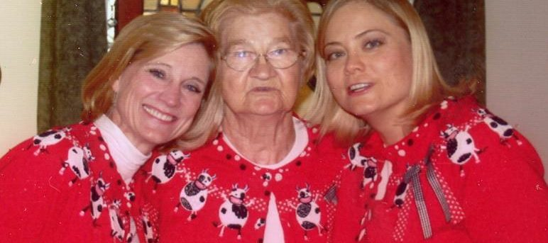 Steph's sister, her mom and Steph. They all have blond hair. Steph's mom, in the middle is wearing glasses. All three are wearing red sweaters with black and white dancing cows just below the collar