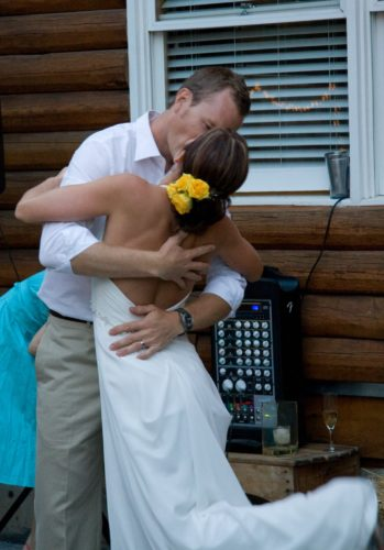 Jen and Matt on their wedding day. Jen is wearing a white wedding dress with yellow flowers in her hair. Her back is to the camera and her arms are around Matt. Matt is wearing a long-sleeve collared white shirt and khaki pants. They are kissing in front of a window with white blinds and a music control panel