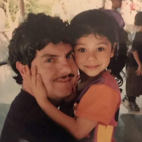 Gracelyn and her dad. Gracelyn is about five wearing a short sleeve orange shirt. Her dad is wearing a black shirt and has a mustache and dark hair