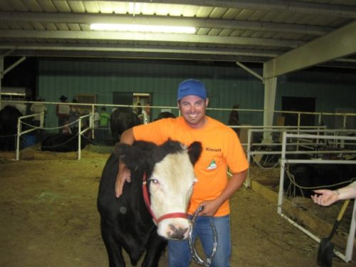 Kyle wearing an orange t-shirt, jeans and a blue baseball cap standing in a pen with a black cow with a white face and a red halter. Kyle's right arm is around the cow.