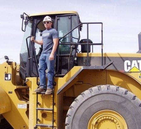 Kyle standing on a large yellow piece of equipment. He's wearing a yellow hard hat, sunglasses, a gray tshirt, blue jeans and brown work boots