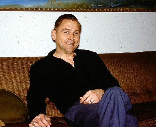 Jerry's dad around age 40? sitting on brown couch wearing a long sleeve black shirt and blue pants