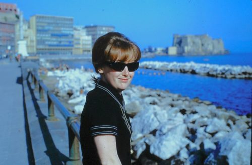Joe's mom standing at a railing. There are rocks and water behind her and behind there there are the buildings of a city. She's got short light brown hair and she's wearing sunglasses and a dark dress with white piping