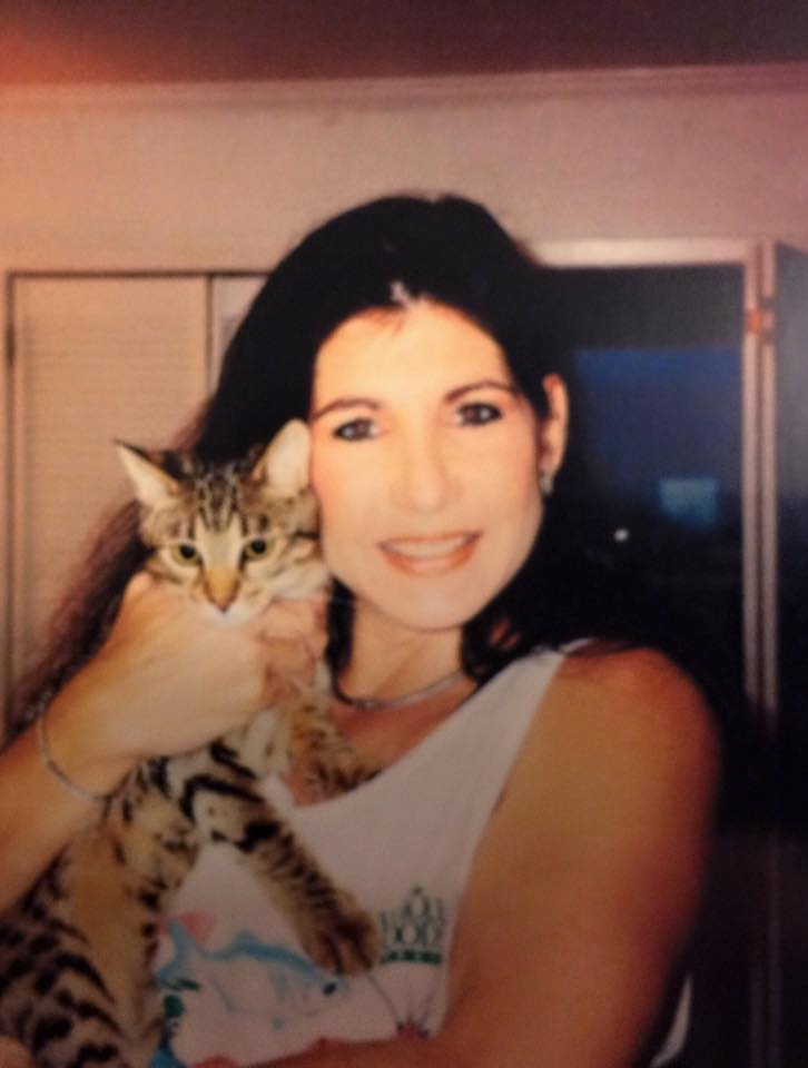 Dana wearing a light champagne tank top and holding a kitten up near her face. Dana's hair is dark, long and parted in the middle.