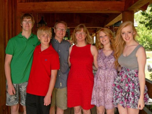 From left to right -- Scott's son wearing glasses, a green polo shirt and grey print shorts; Scott's other son wearing a red polo shirt and navy blue pants; Scott wearing glasses, a dark gray button shirt with a color and khaki shorts; Judy wearing glasses and a red dress; Scott's daughter wearing a purple print sundress; Scott's other daughter wearing a sundress with a gray bodice and a floral print skirt. They all have reddish blond hair