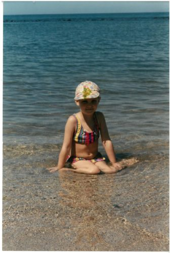 Alexandra sitting in the shallow water at a beach or lake. She's wearing a print baseball cap and a colorful bikini