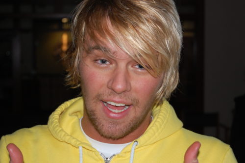 Conner has long blond hair parted to the left side. His face has five day grown on it. He's wearing yellow zip sweatshirt and a white t-shirt underneath