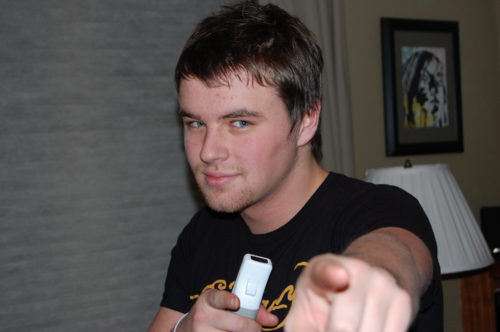 Conner pointing his left pointer finger at the camera. He's wearing a black t-shirt with yellow writing on it and holding a white controller in his right hand