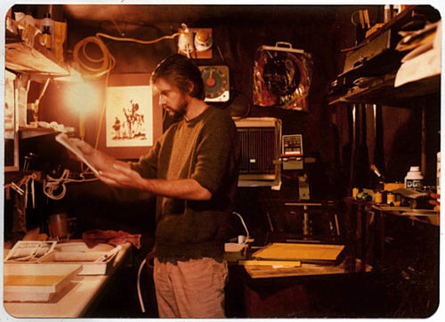 Cliff in the darkroom. The photo is sepia colored. Cliff has a beard and lighter colored pants on. His sweatshirt is darker than his pants and the sleeves are pushed up to just below his elbows
