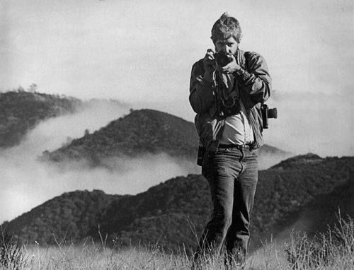 Black and white photo of Cliff on a hillside point his camera at the camera with another over his left shoulder. His shirt is lighter in color than his jacket