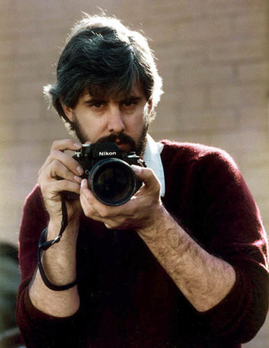 Cliff holding a camera pointed at the camera. He has dark hair and a beard and is wearing a maroon sweater pulled up to his elbows and a white collar shirt underneath